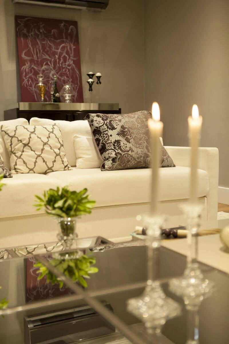 Detalhes da decoração da mesa de centro, composta por castiçais e vasos de cristal.