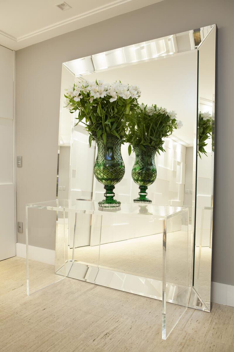 Hall de entrada com espelho e aparador de acrílico.