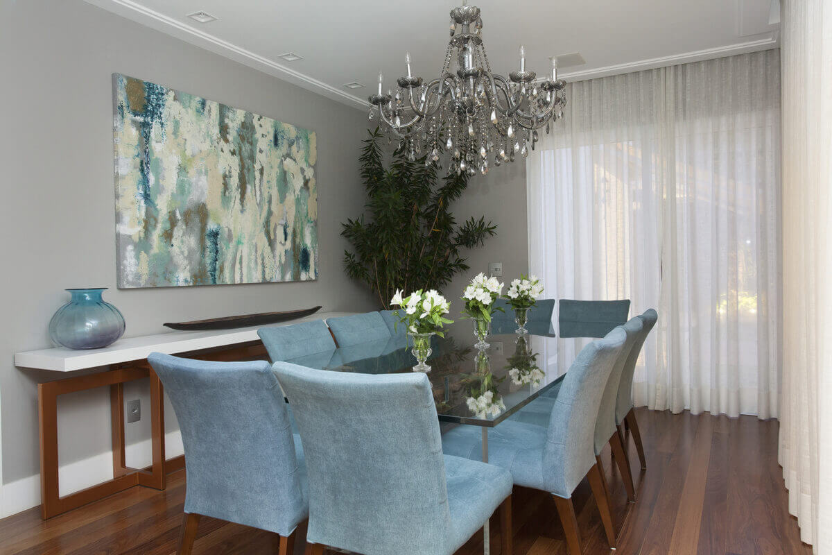 Sala de jantar com mesa de vidro e dormentes. Lustre de cristal e aparador com pés de cobre.