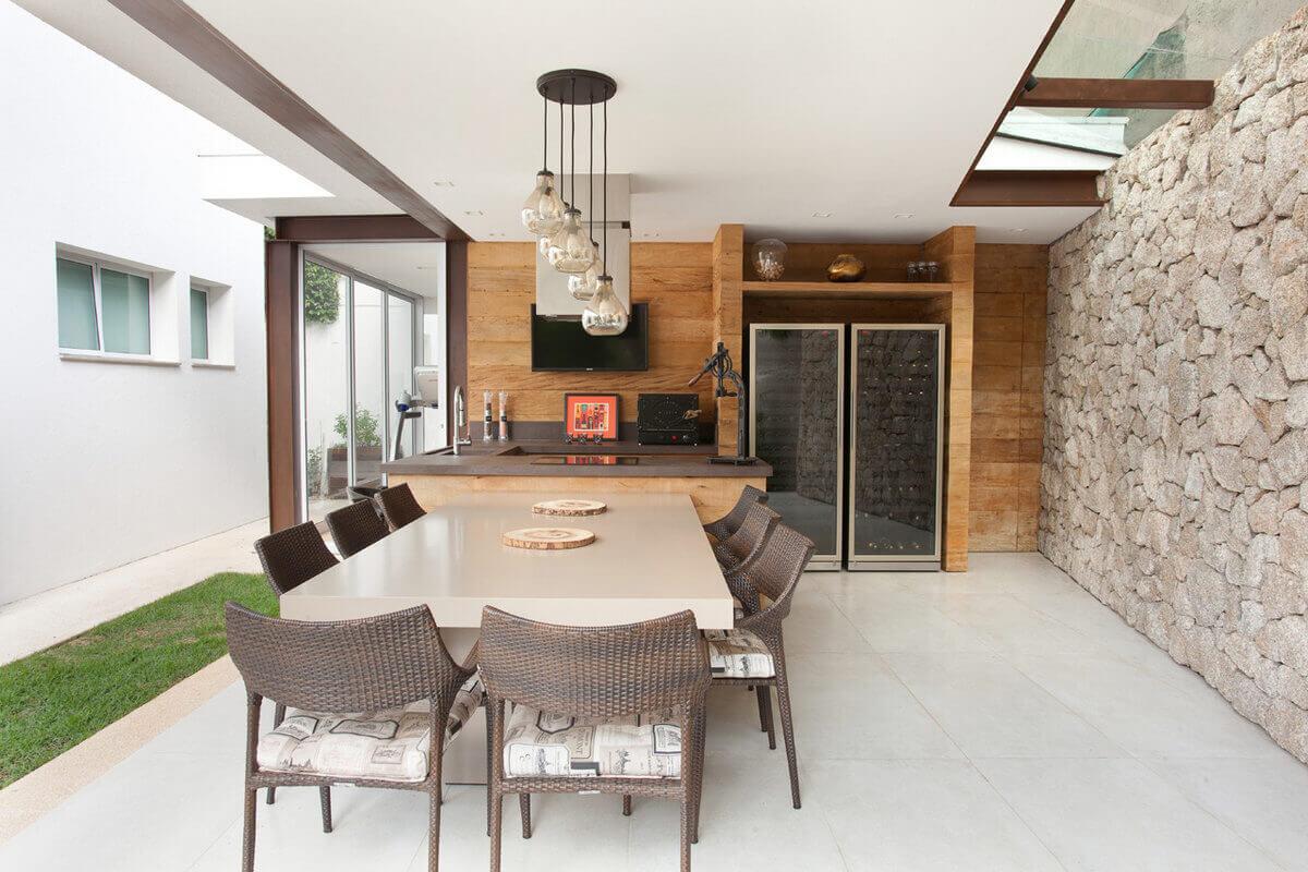 Anexo gourmet com adega. Construído com estrutura de aço corten, o telhado de vidro ilumina o muro de pedra moledo.