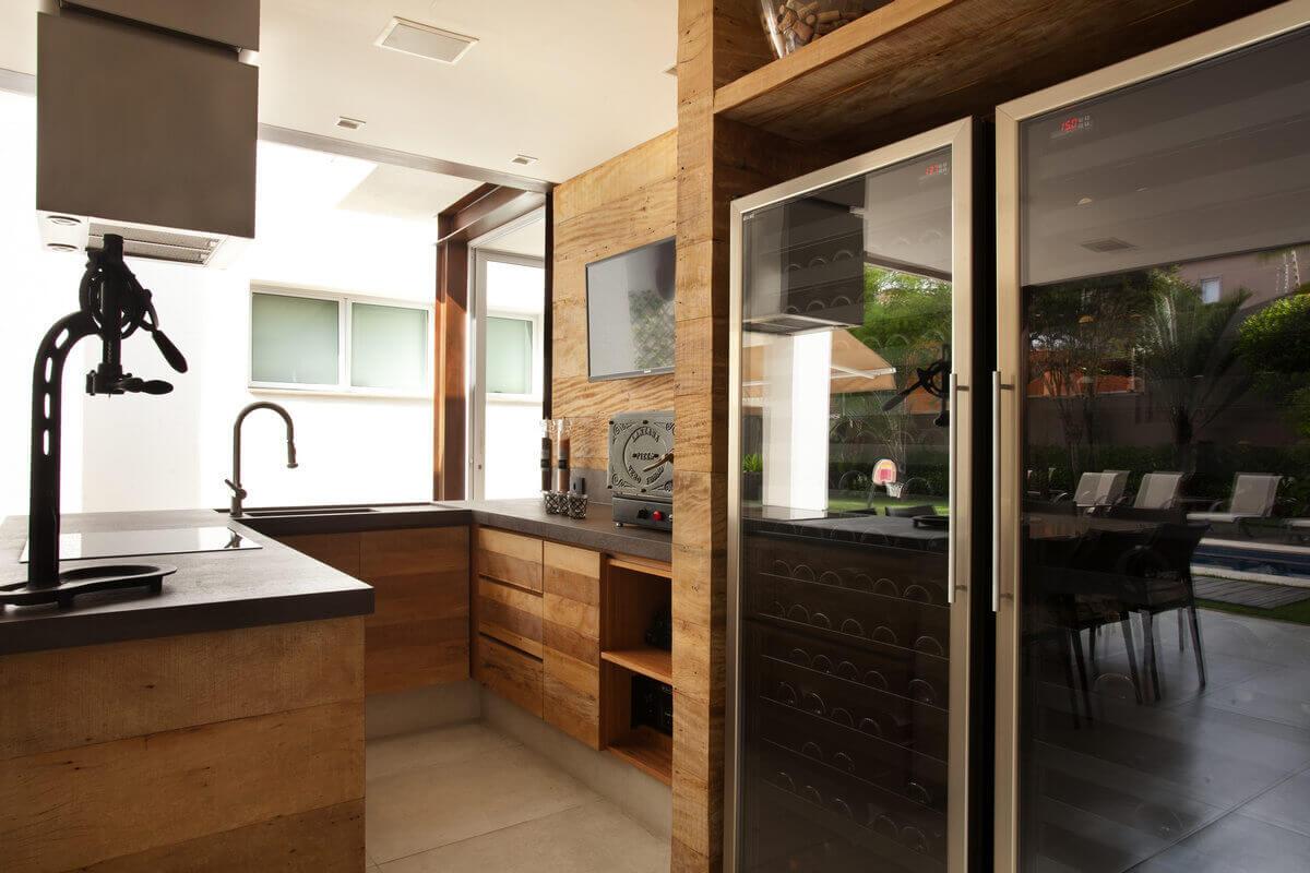 Área Gourmet de residência em São Paulo. Destaque para as adegas de 200 garrafas, encaixadas num nicho de madeira de demolição.