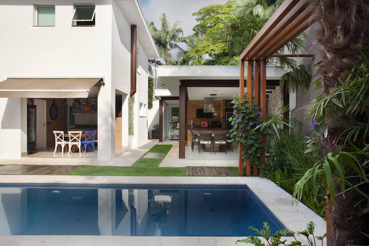 Anexo para adega gourmet, aberto para o jardim e para piscina, integrando a região ao ambiente da churrasqueira.