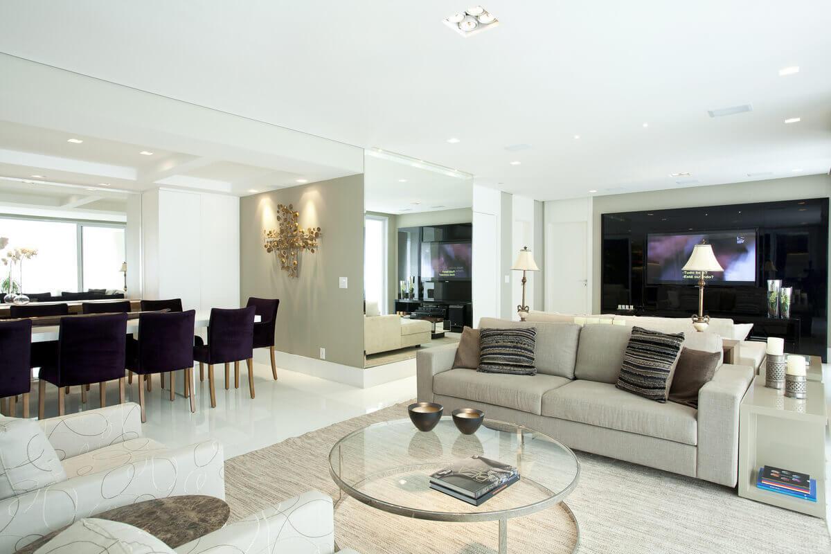 Nas salas onde o branco predomina no piso em marmoglass, as paredes na cor bege e o painel de TV em laca preta são um destaque especial.