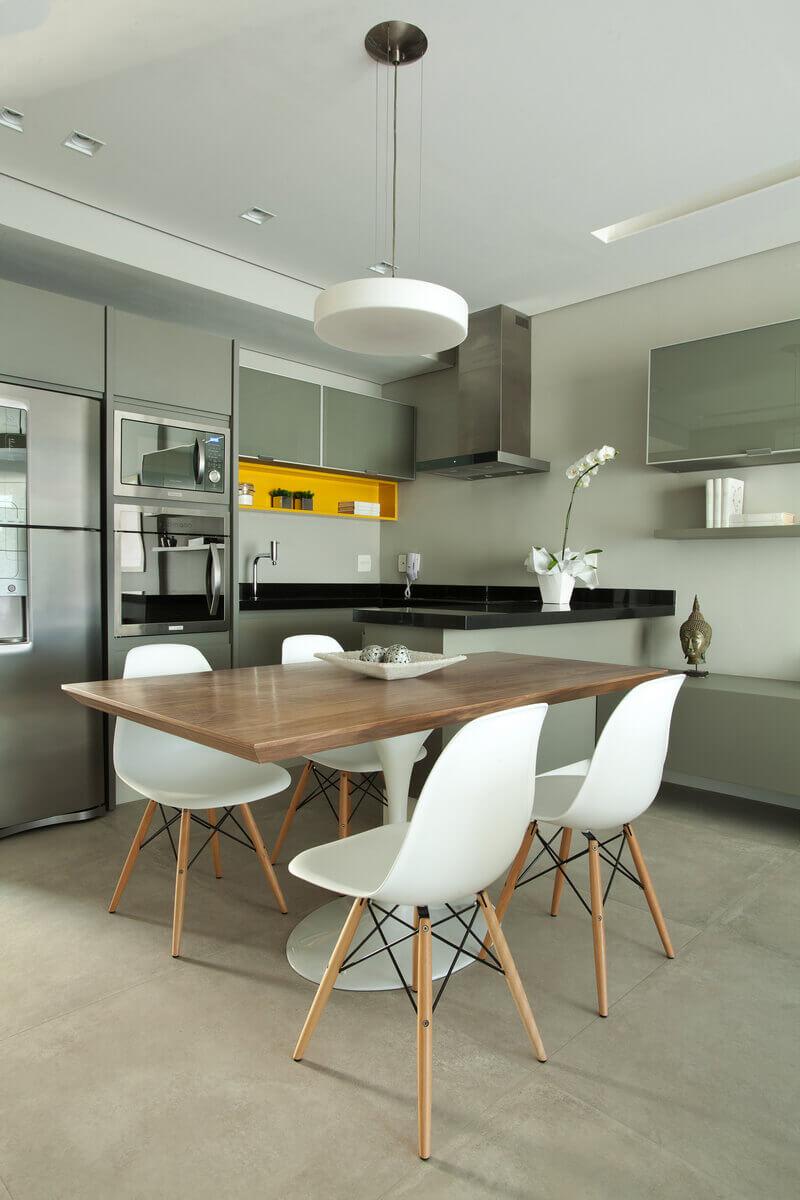 A mesa de jantar neste loft de 67m² em madeira está acoplada à bancada da cozinha e esquenta o ambiente.