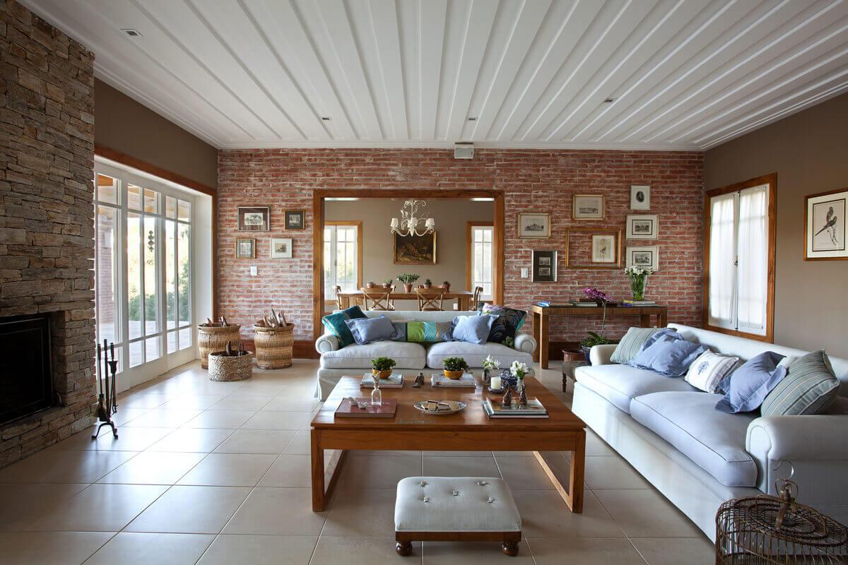 Sala de estar com paredes de tijolos rústicos, lareira de pedra madeira e forro de gesso saia e blusa.