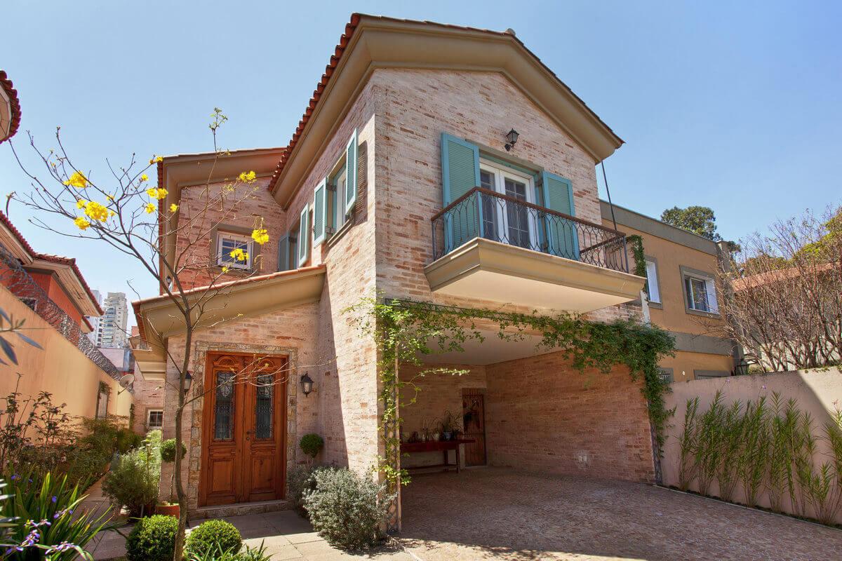 Casa com arquitetura Provençal com fachadas em tijolos de demolição caiados e caixilharia com venezianas verdes.