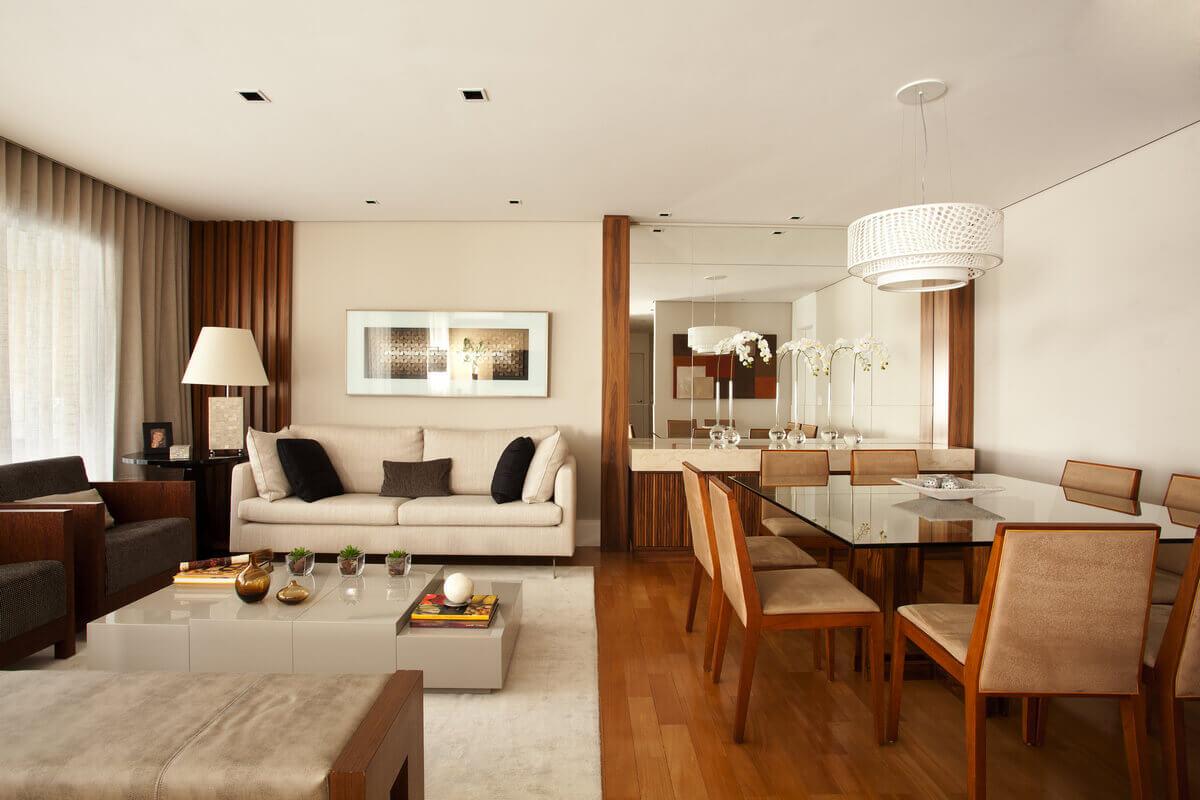 Painel de freijó com ripas e colunas de madeira delimitam as salas de estar e jantar. O espelho sobre o aparador de mármore confere amplitude aos ambientes.
