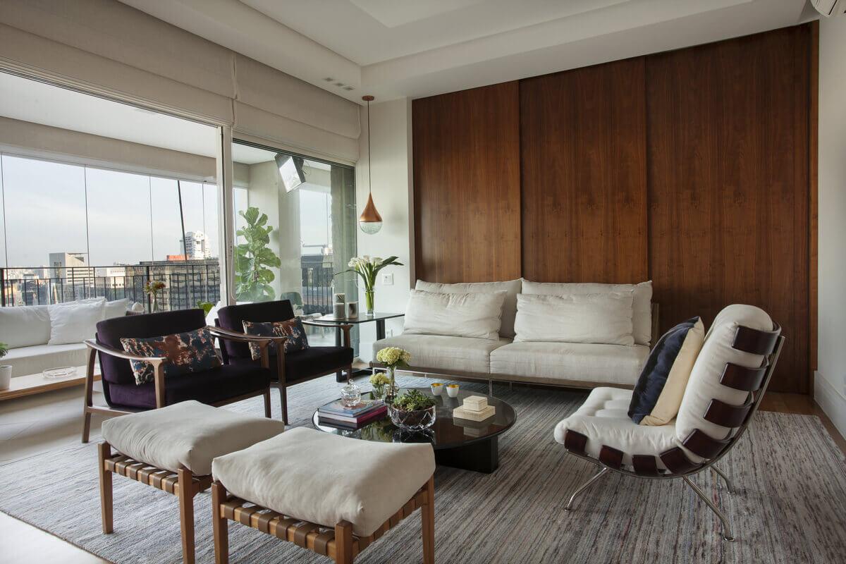 Sala integrada com varanda com painéis de madeira.