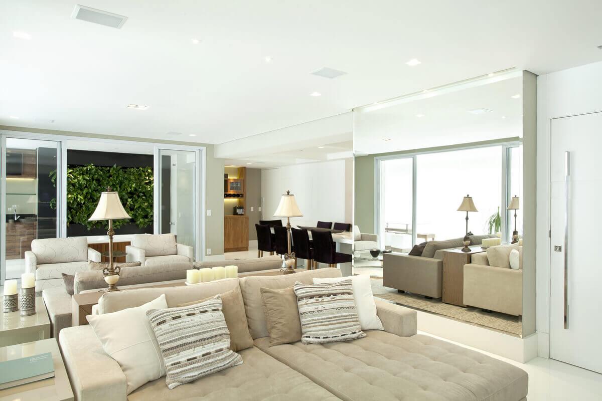 Salas integradas com cores claras, onde o branco e o bege predominam. Ao fundo, jardim vertical realçado com moldura preta.