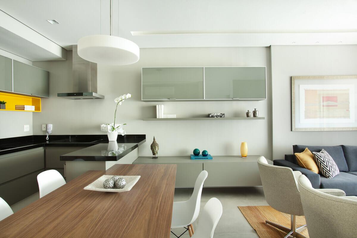 Sala e cozinha integradas e separadas pela mesa de jantar de madeira com base da Saarinen.