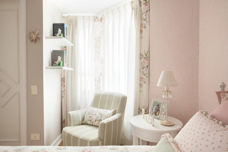 Cantinho de leitura com tecidos florais e papel de parede.