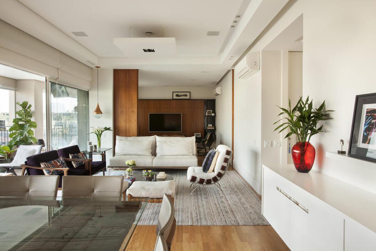 Sala ampla com living, jantar e home theater integrados e separados por painel de madeira deslizante.