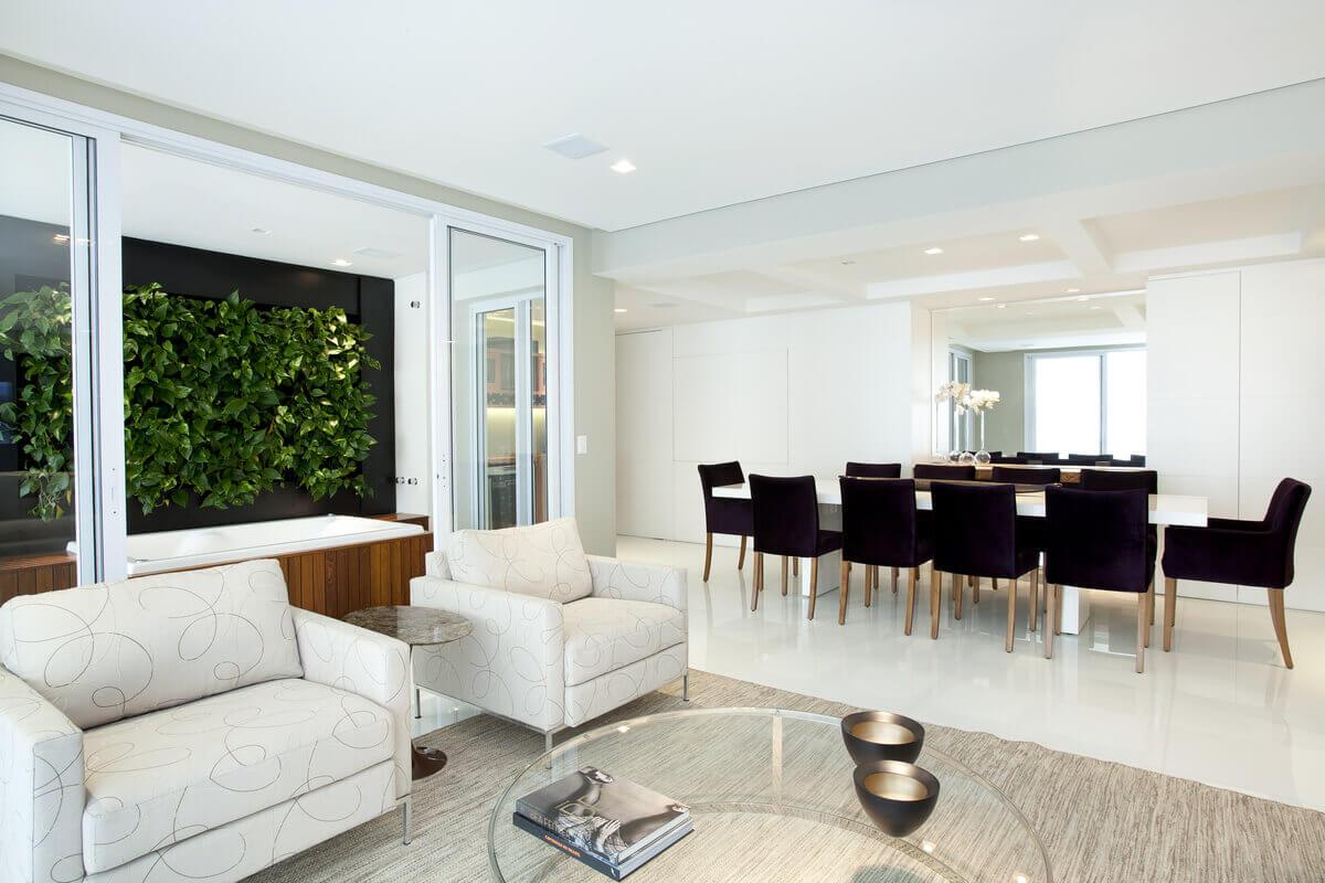 Salas integradas com piso em marmoglass. Ao fundo, painel da sala de jantar e na varanda, jardim vertical sobre SPA.
