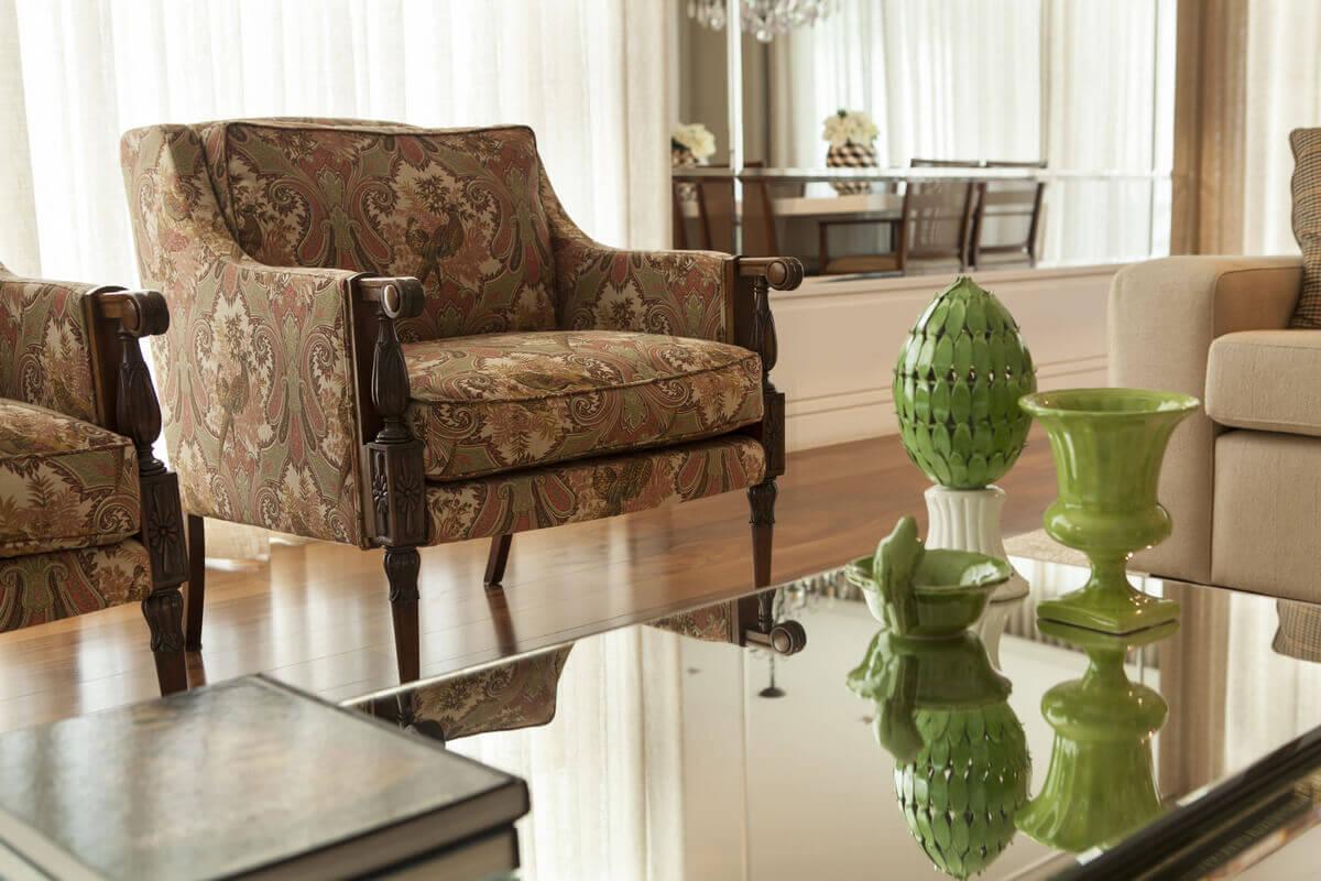 Detalhes das poltronas em estilo inglês da Jocal. Móveis com tecidos da Entreposto e mesa de centro com composição de peças de cerâmica verde.
