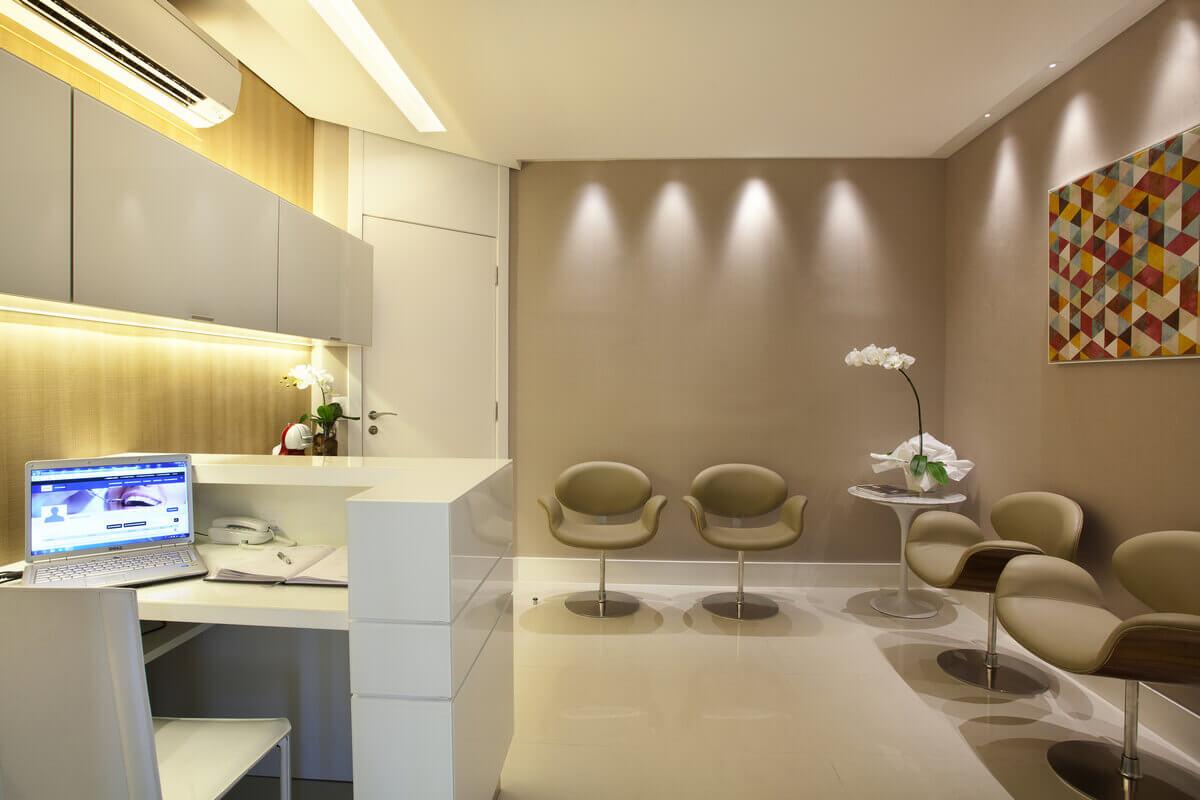 Recepção de consultório dentário com paredes revestidas em papel de parede. Destaque para o efeito das luminárias na parede.