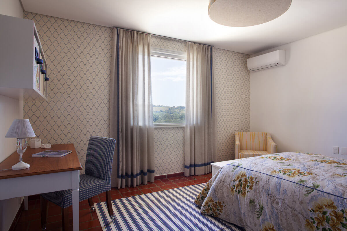 Quarto com cortinas em linho sobre parede revestida com papel de parede, em composição com o tapete listrado.
