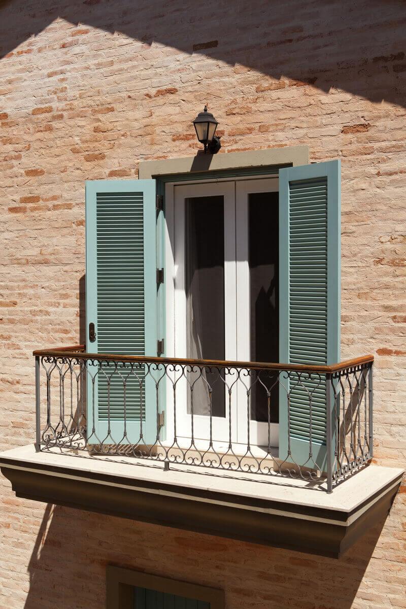 Sacada do quarto com gradil de ferro e Pinho de Riga, desenhados pela arquiteta. Caixilharia pintadas de branco com venezianas verde.