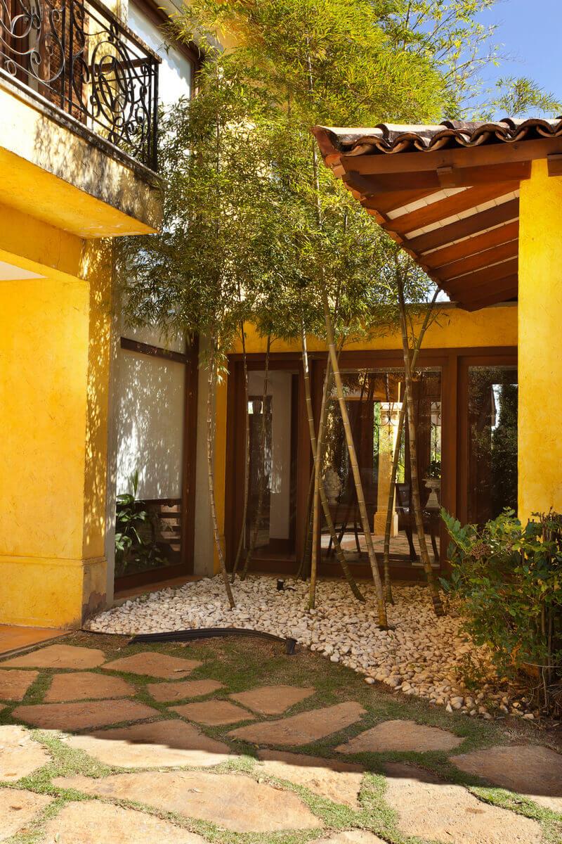 Jardim de bambus como plano de fundo do hall de entrada e da escada.