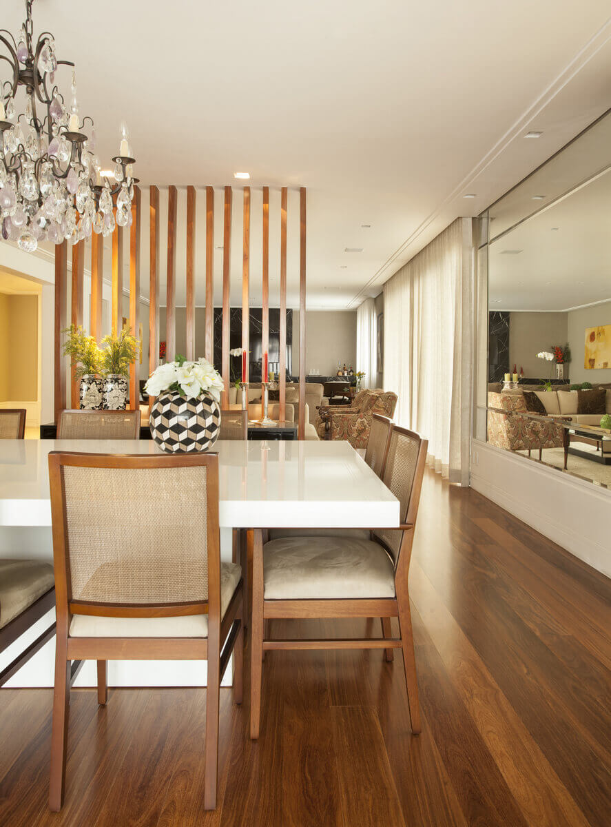 Sala de jantar com mesa em mármore branco. Destaque para o lustre de cristal de rocha e para o biombo de madeira.