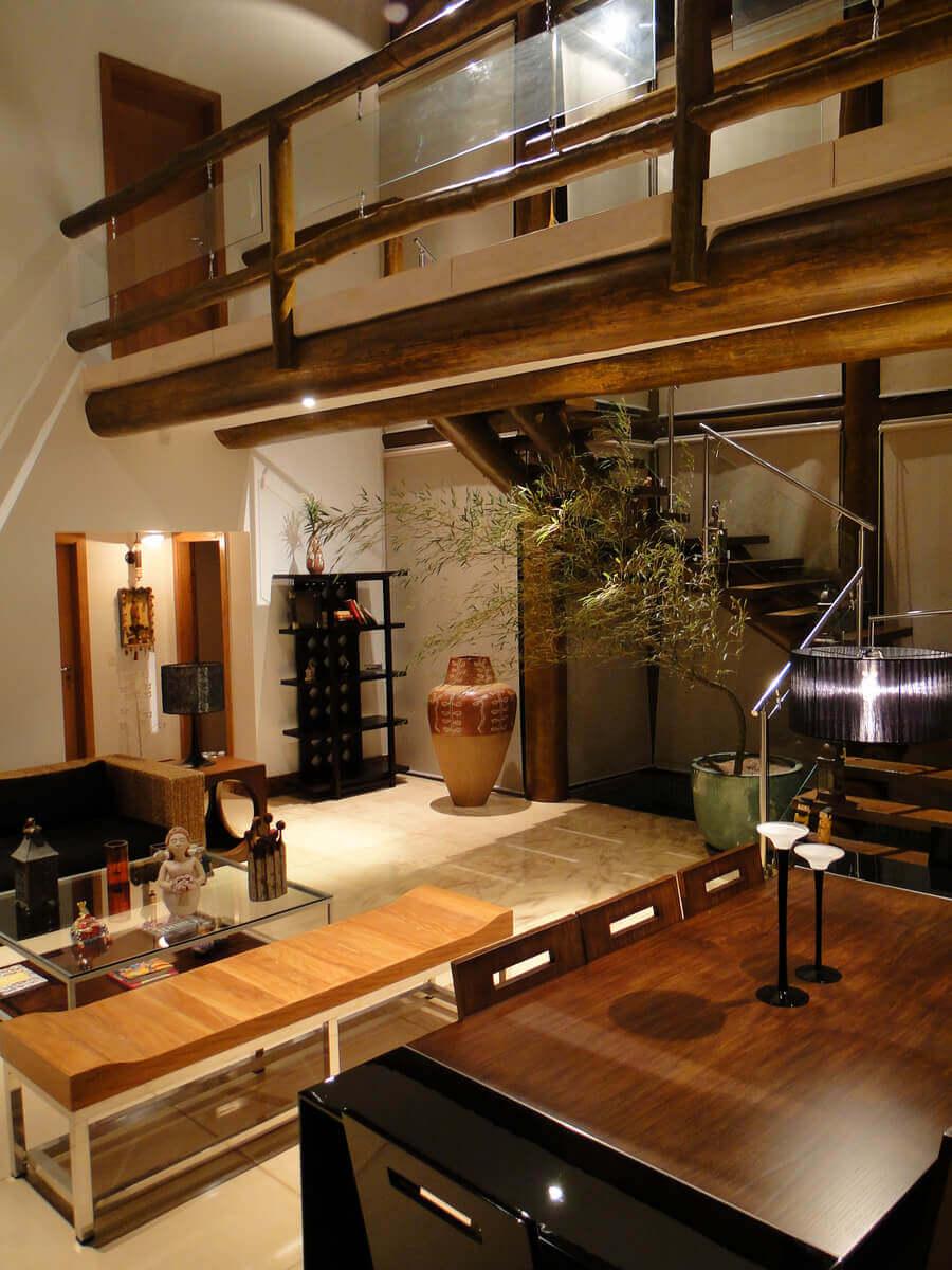 Sala de estar com destaque para escada com degraus e guarda-corpo de eucalipto.