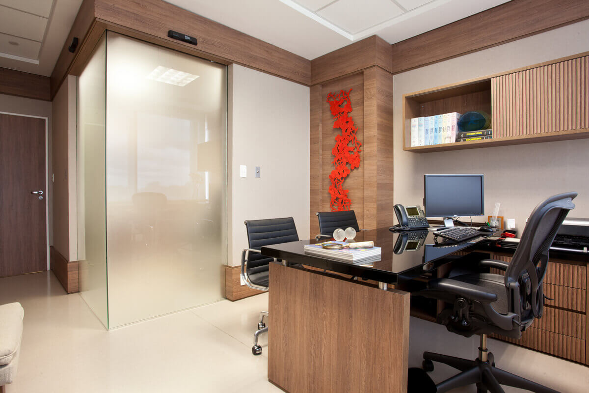 Consultório médico com sala de exames separada por porta de correr de canto em vidro jateado.