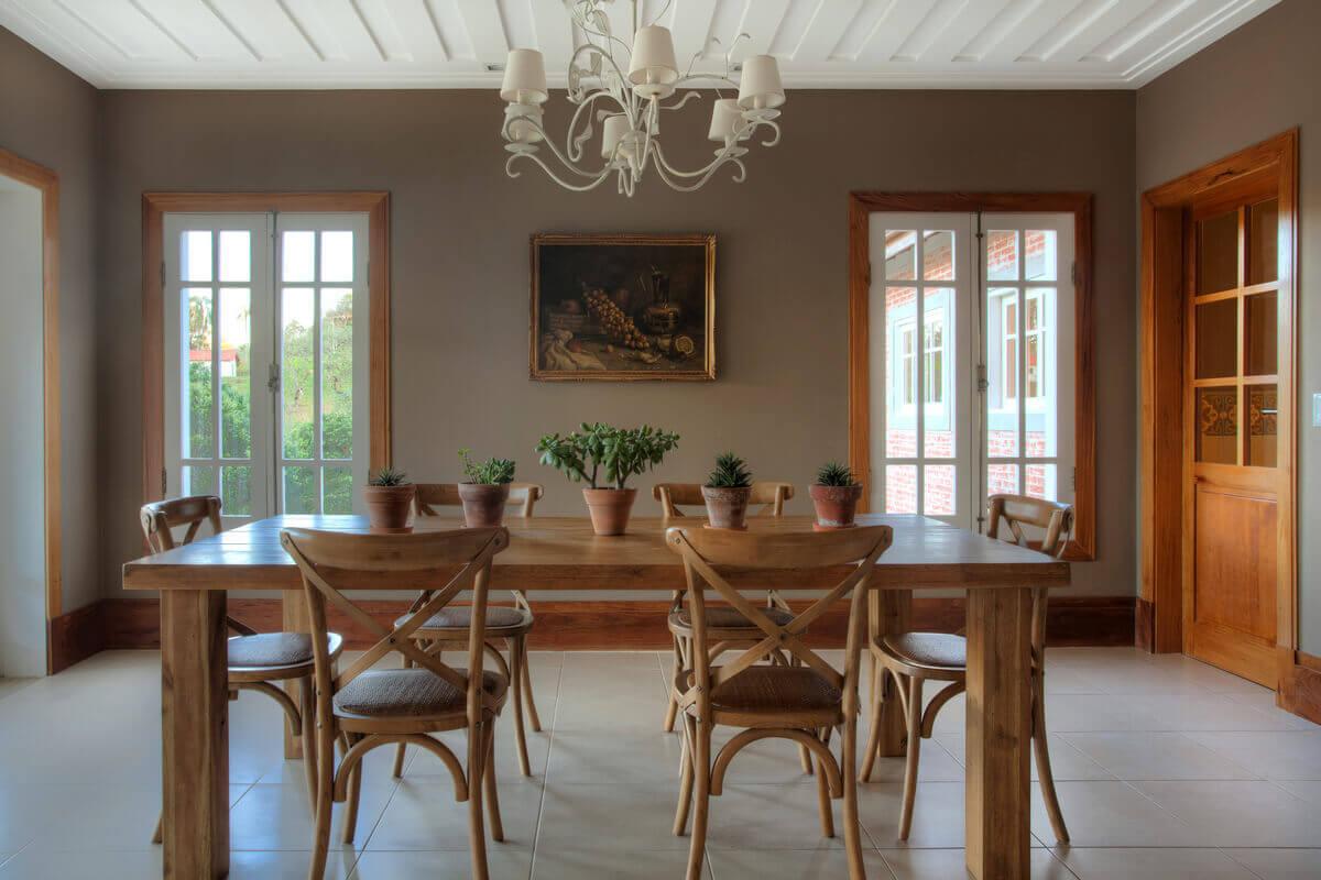 Sala de jantar com janelas brancas ao fundo com guarnição de freijó e forro de gesso modelo saia e blusa.