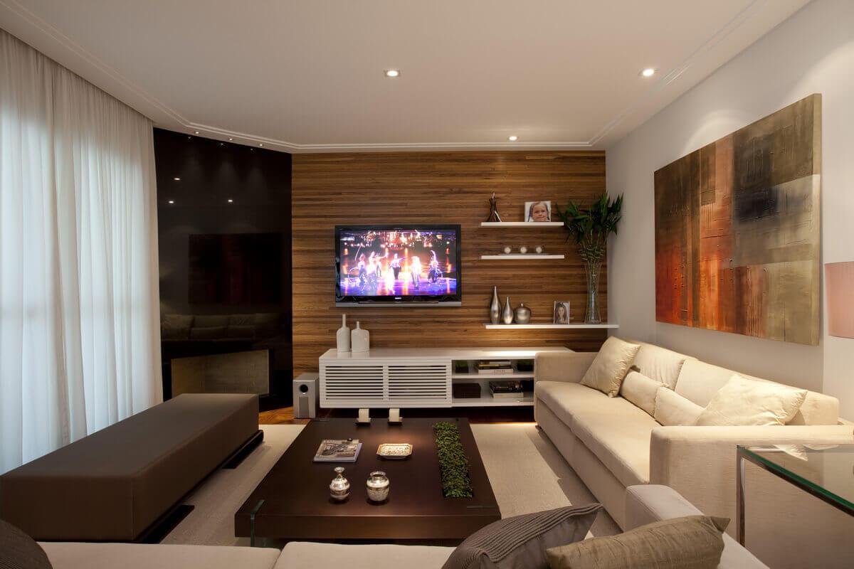 Neste Home Theater, a parede foi revestida com painel de Nogueira. O móvel e prateleiras revestidos em laca emolduram a TV. A lareira foi revestida em granito preto.