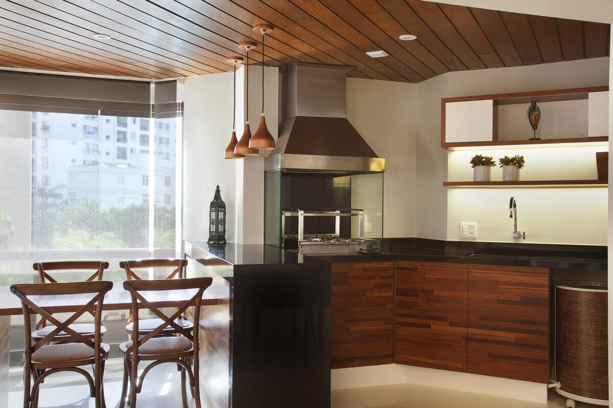 Na varanda integrada, a churrasqueira é a estrela da área gourmet. Gabinetes em cumaru palito e tampos em granito preto.