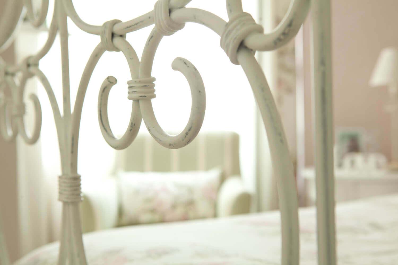 Detalhe da cama em ferro patinado em quarto feminino - estilo romântico.