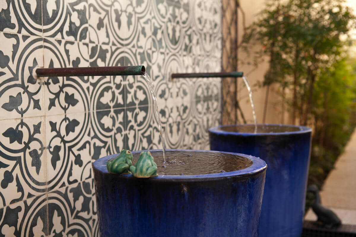 Detalhe do corredor lateral, onde duas bicas saem da parede de ladrilho hidráulico jorrando água em vasos azuis, que transbordam em um espelho d'água.