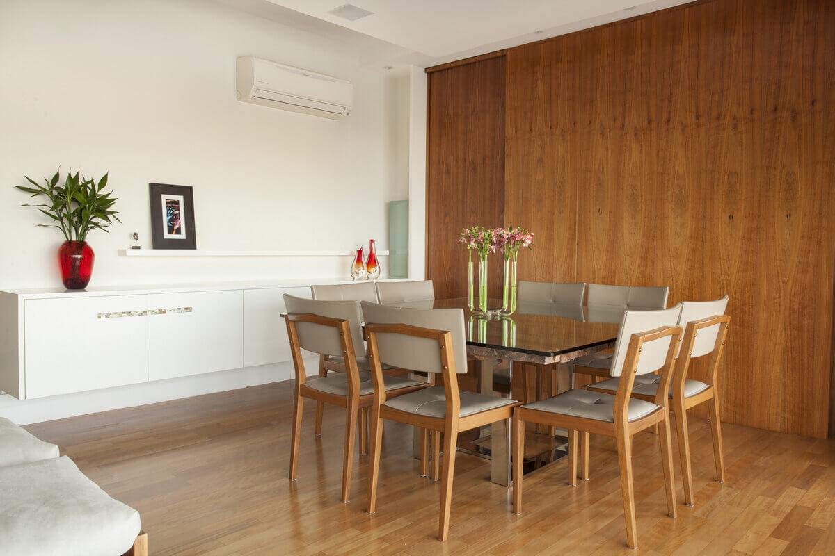 Sala de jantar com buffet suspenso e painel de madeira separando a cozinha.