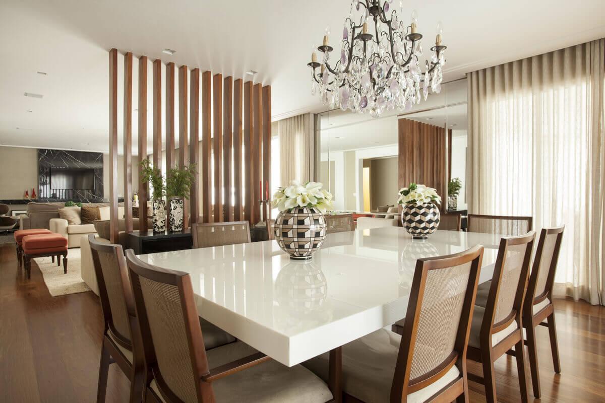 Sala de jantar com mesa em marmoglass e espelho bisotado, separada do living por biombo de madeira.