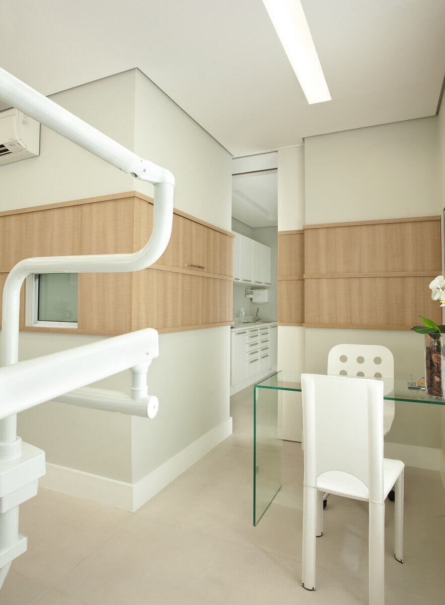Paredes com faixa em madeira ocultando um armário e emoldurando as janelas de comunicação com a sala de esterilização.