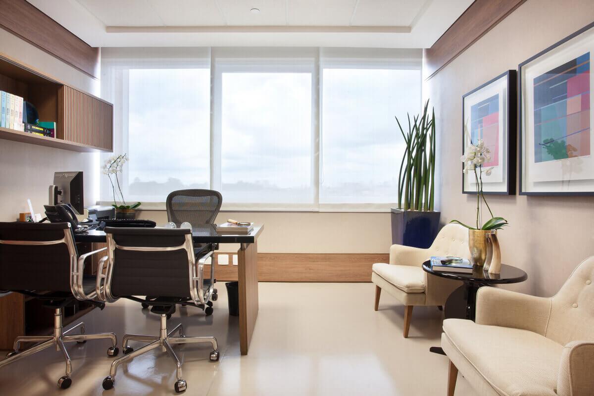 Consultório médico no Hospital Einstein. Papel de parede entre rodapés e roda-tetos altos. Mesa com tampo preto.