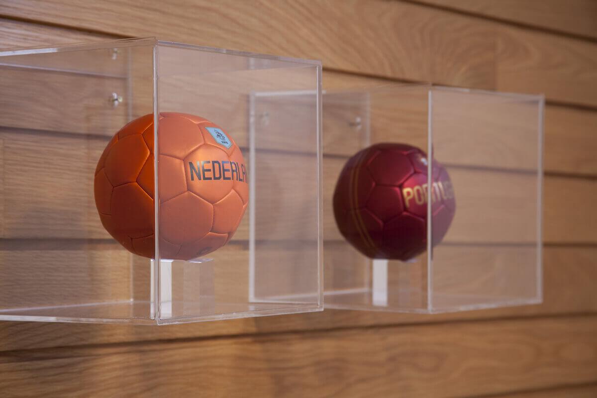 Detalhes das caixas de acrílico para coleção de bolas fixadas em painel de madeira.
