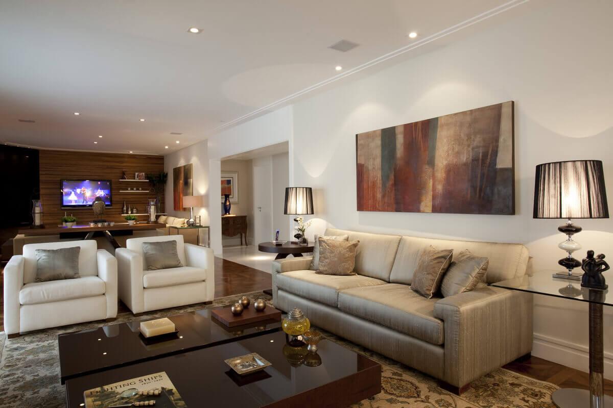 Sala de apartamento no Panamby, com sofá bege de seda, poltronas Cru e mesas de centro e laterais da Artefacto.