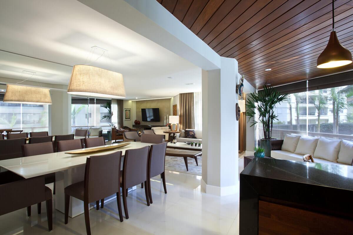 Integração da varanda com a sala, com unificação dos pisos com Porcelanato Marmi Carrara Bianco da Portobello. Sala de jantar com lustre da Bertolucci e espelho em toda parede.