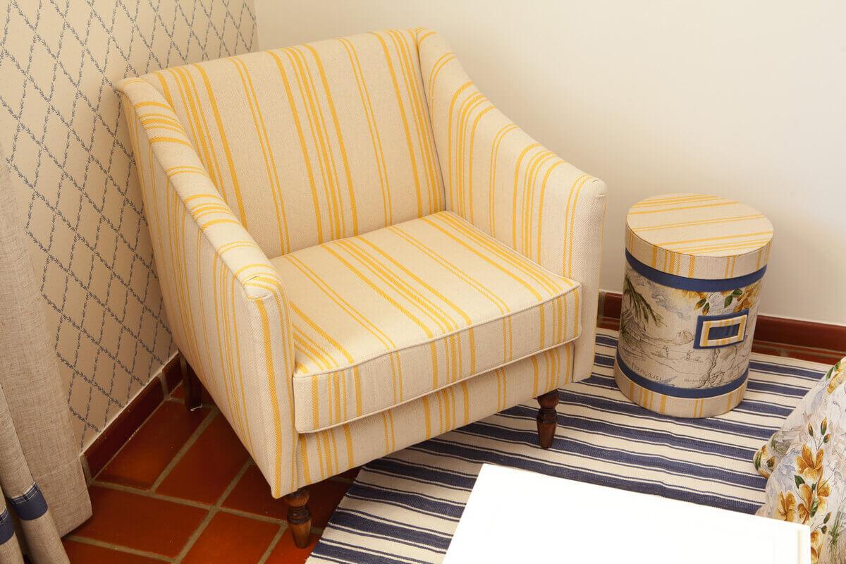 Canto da poltrona com caixa cilíndrica revestida em tecido do Cecília Nucci Ateliê, servindo como mesa lateral.