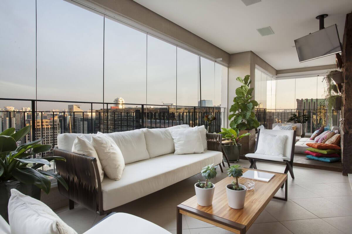 Varanda integrada à sala com vista para skyline da cidade. Mesa com champanheira desenhada pela arquiteta.