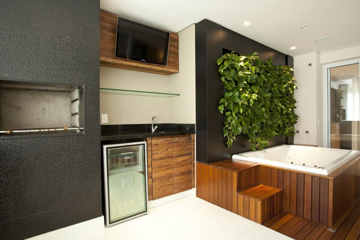 Varanda com churrasqueira em porcelanato preto, madeira de demolição e SPA com painel de jardim vertical.