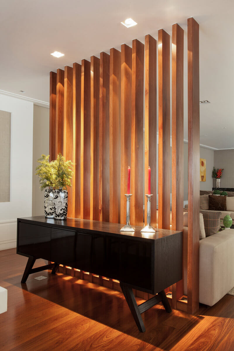 Biombo em madeira com iluminação entre as réguas, servindo de pano de fundo para o buffet e separando o living da sala de jantar, mantendo-os integrados.