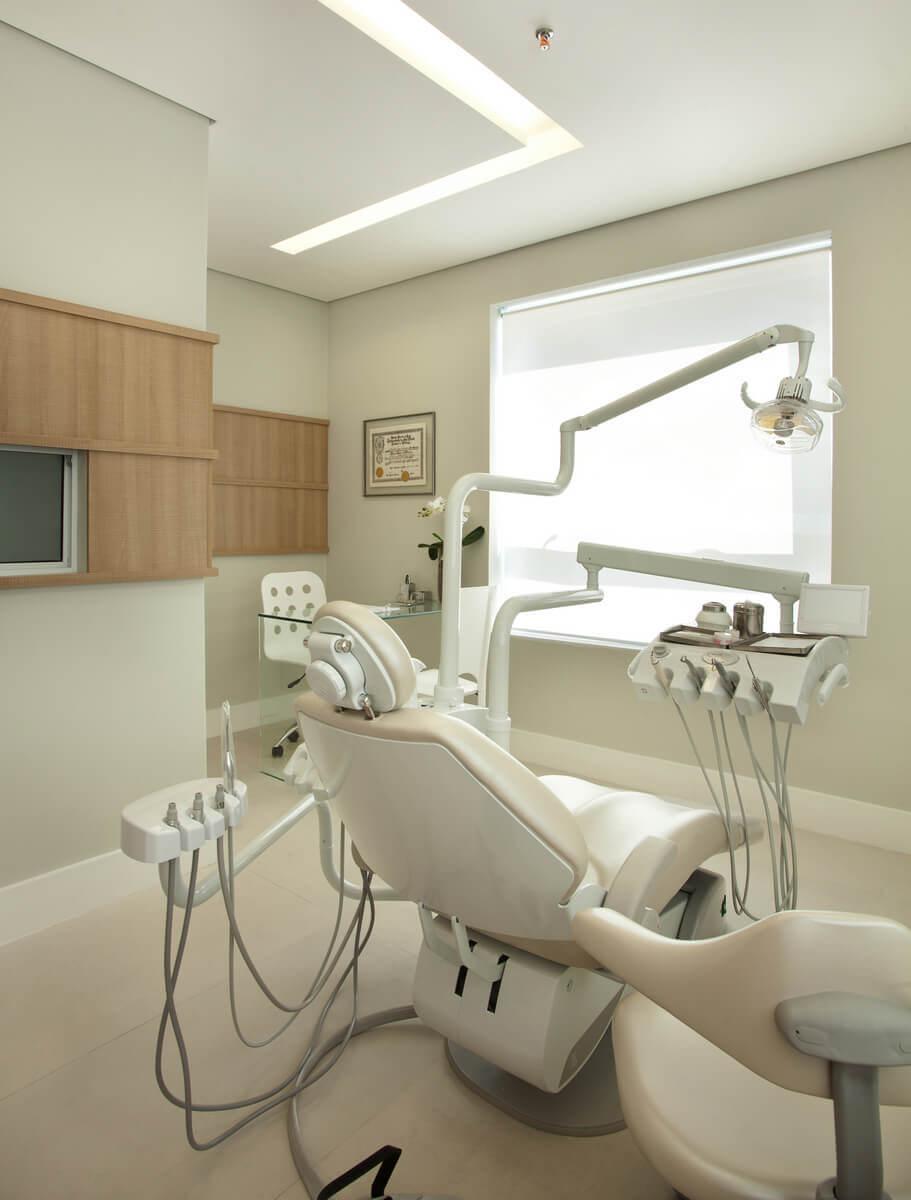 Sala de consulta com cadeira de dentista e mesinha para atendimento.