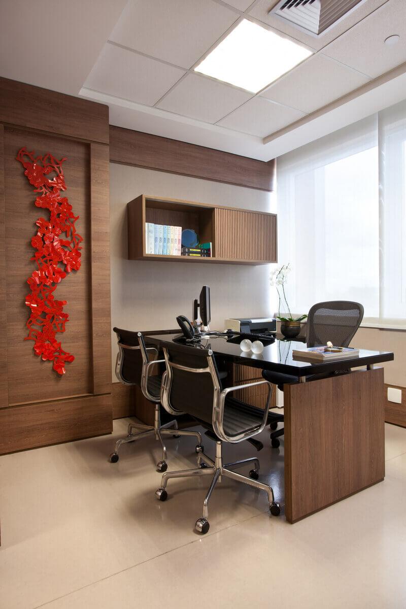 Mesa do médico em consultório no Hospital Albert Einstein. Marcenaria de madeira de nogueira com tampo preto. Escultura de Jocimar Tavares.