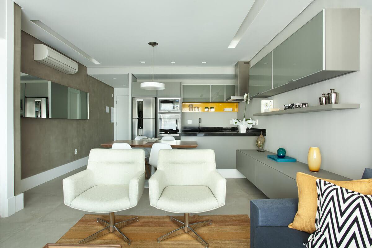 Cozinha aberta para sala com armários em vidro cinza e nicho em laca amarela.