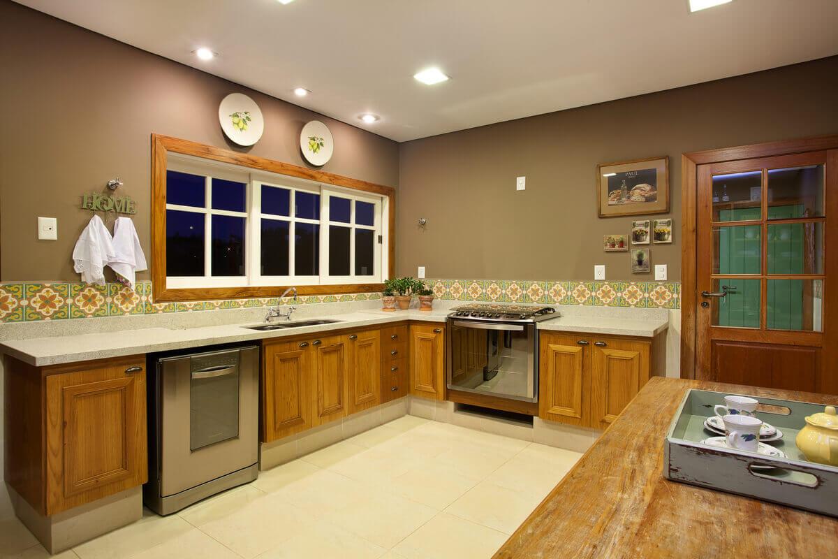 Cozinha rústica com faixa em ladrilho hidráulico e armários em freijó.