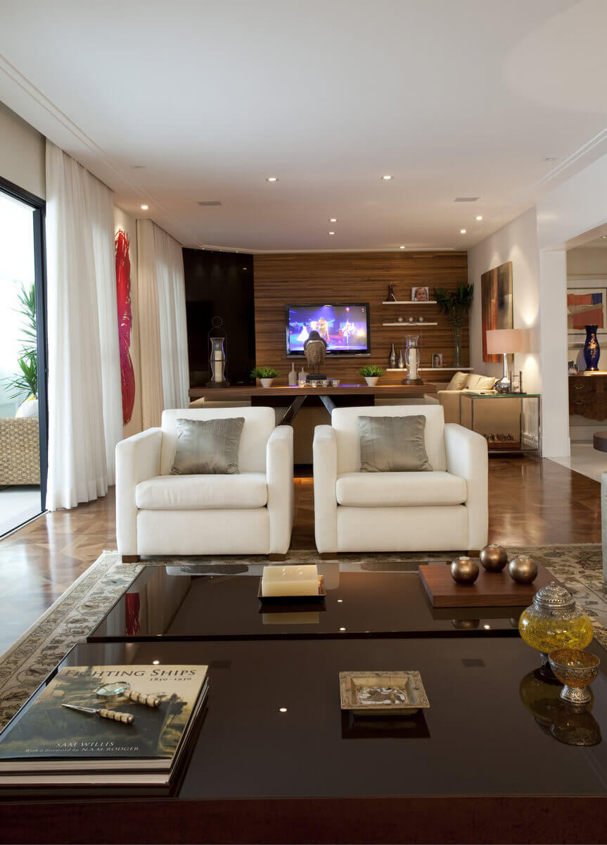Sala de estar com destaque para o par de poltronas Cru e para as mesas de centro marrons.