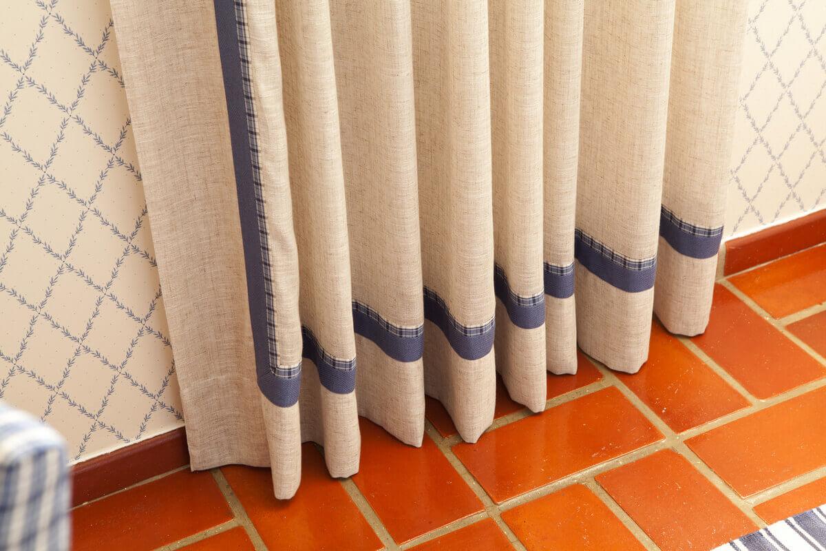 Barra e faixa lateral da cortina fazem composição com as almofadas da cama.