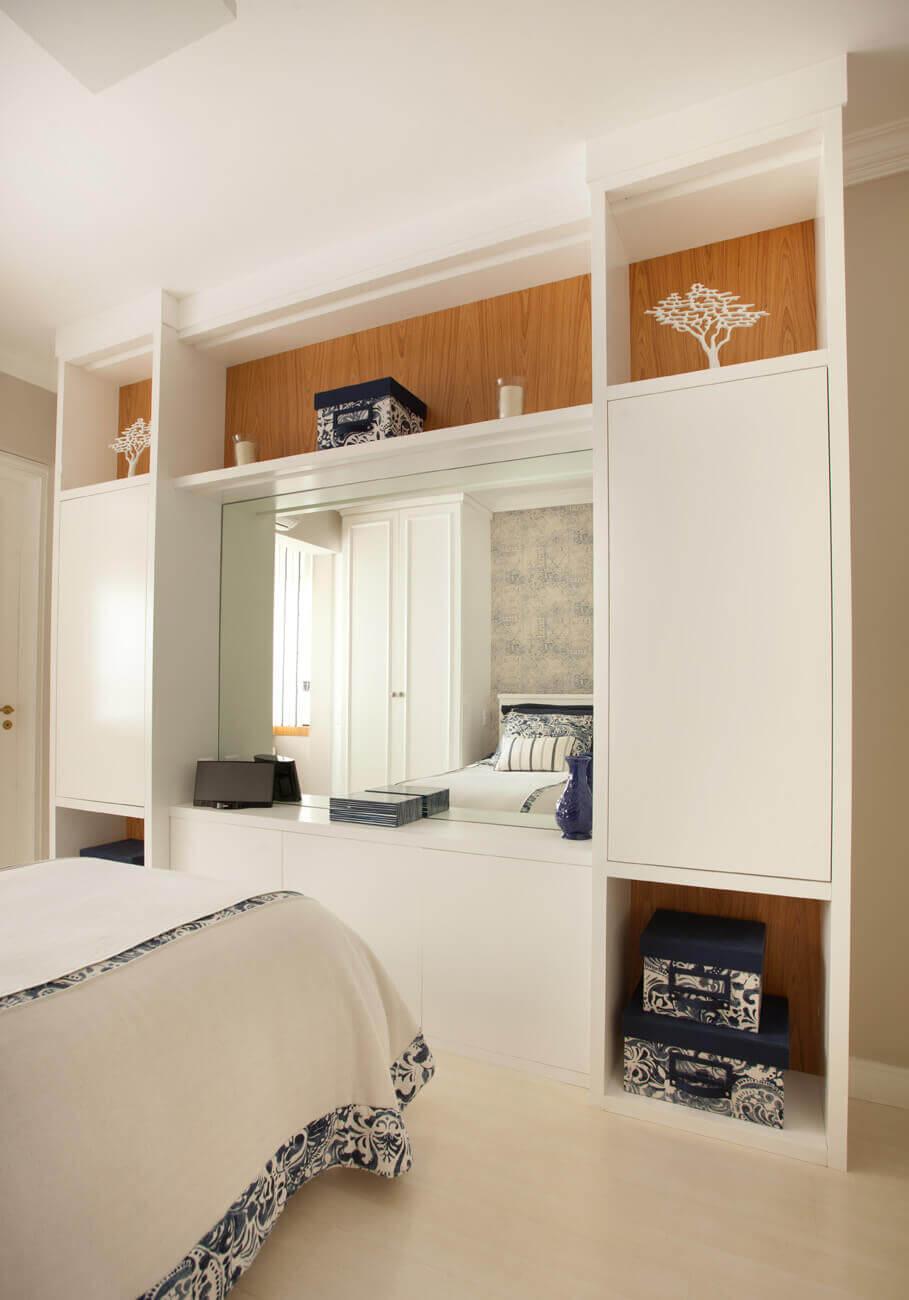 Estante em laca branca com fundo em freijó e espelho em quarto feminino.