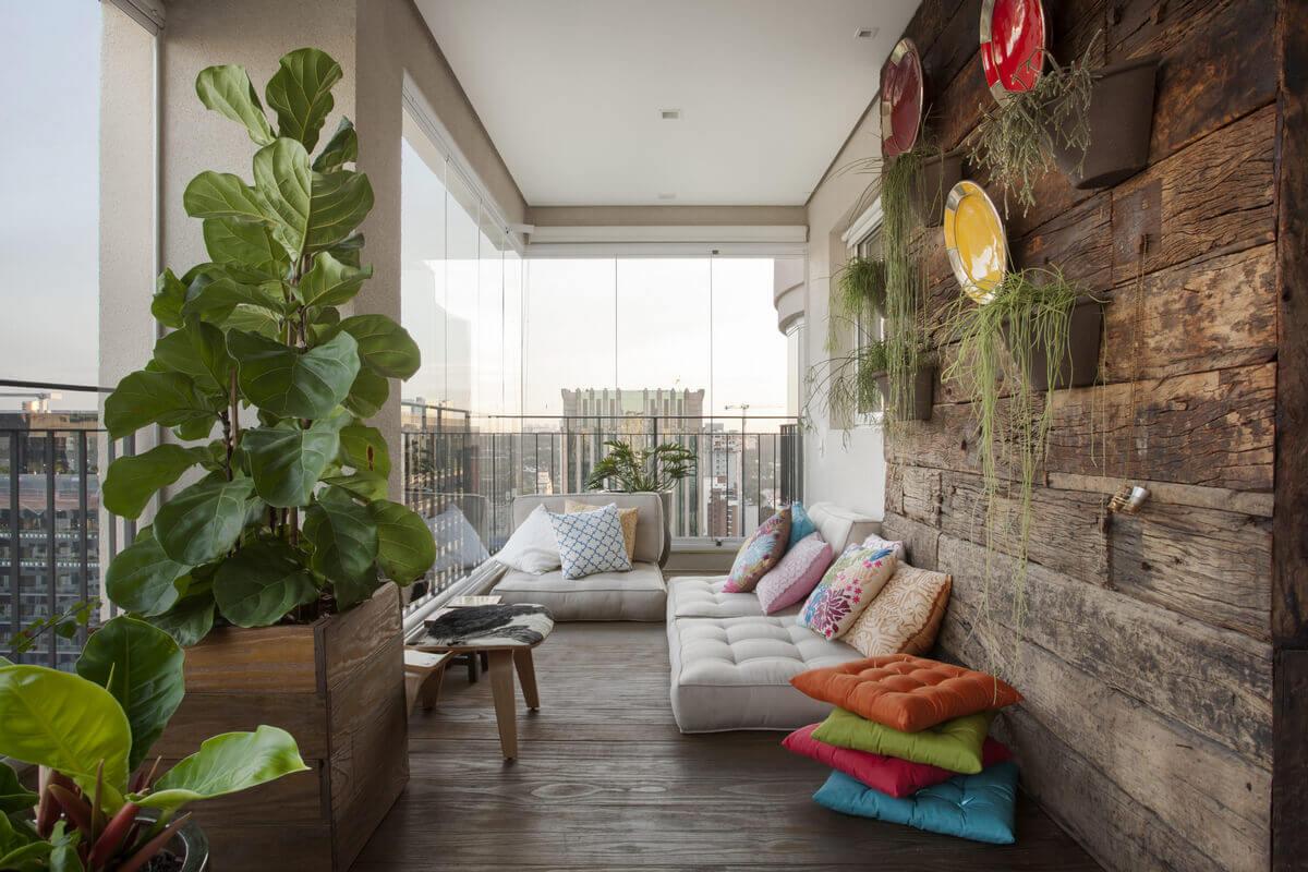 Canto da varanda com futons sobre o deck e painel de madeira de demolição.