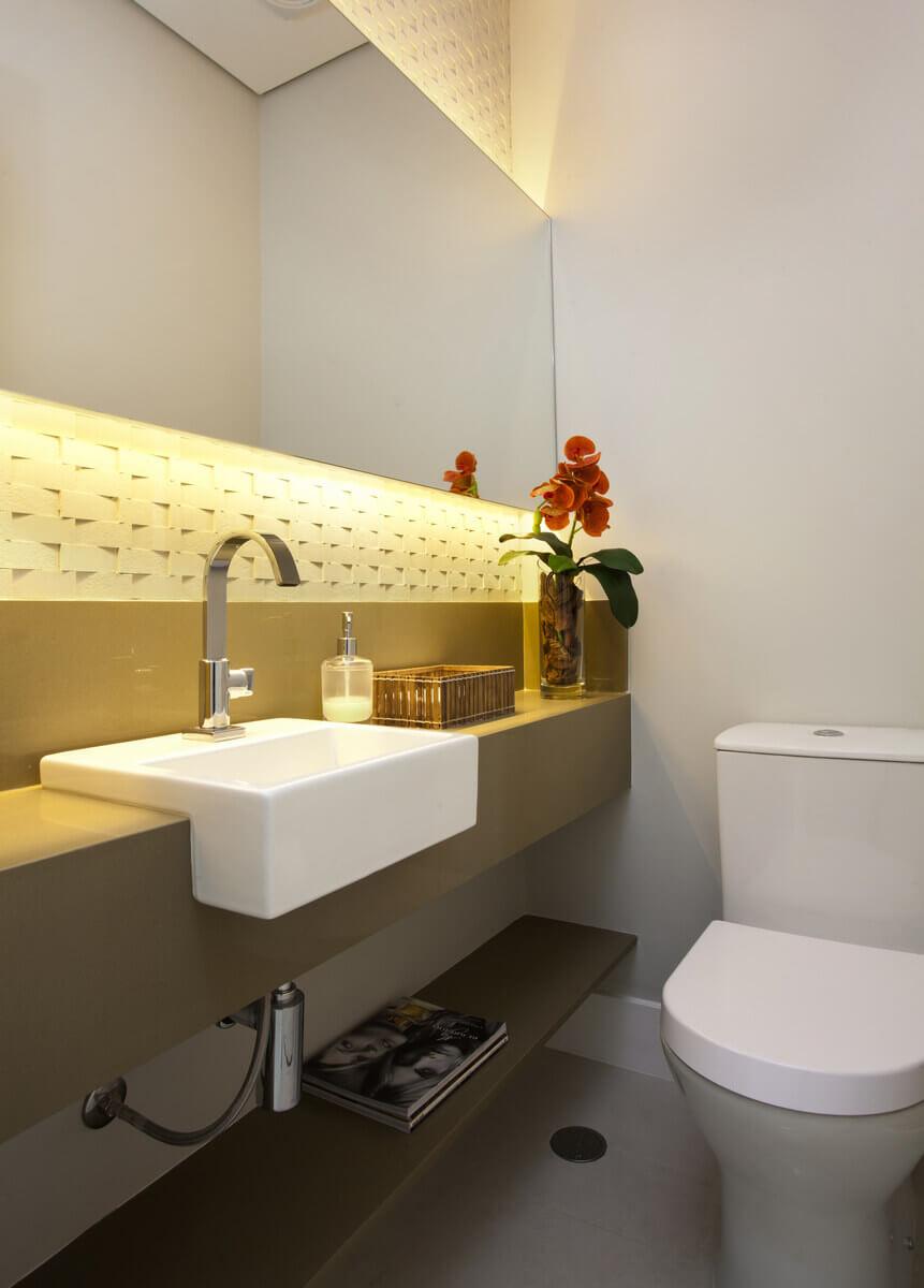 Lavabo com parede revestida com mosaico cimentício e espelho afastado com fita de LED por trás.